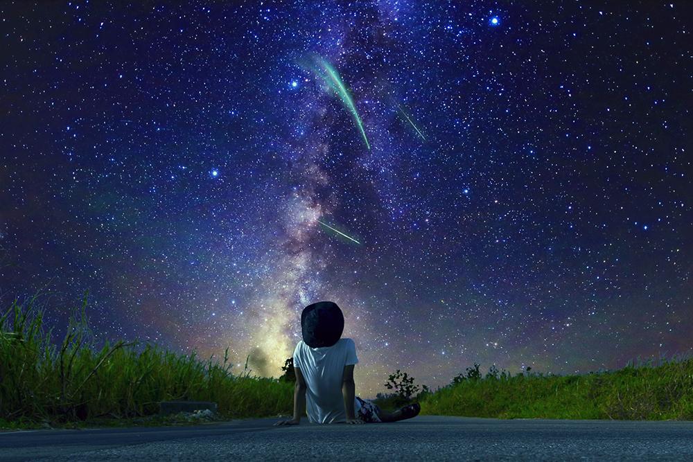 道に座って星空を見る男